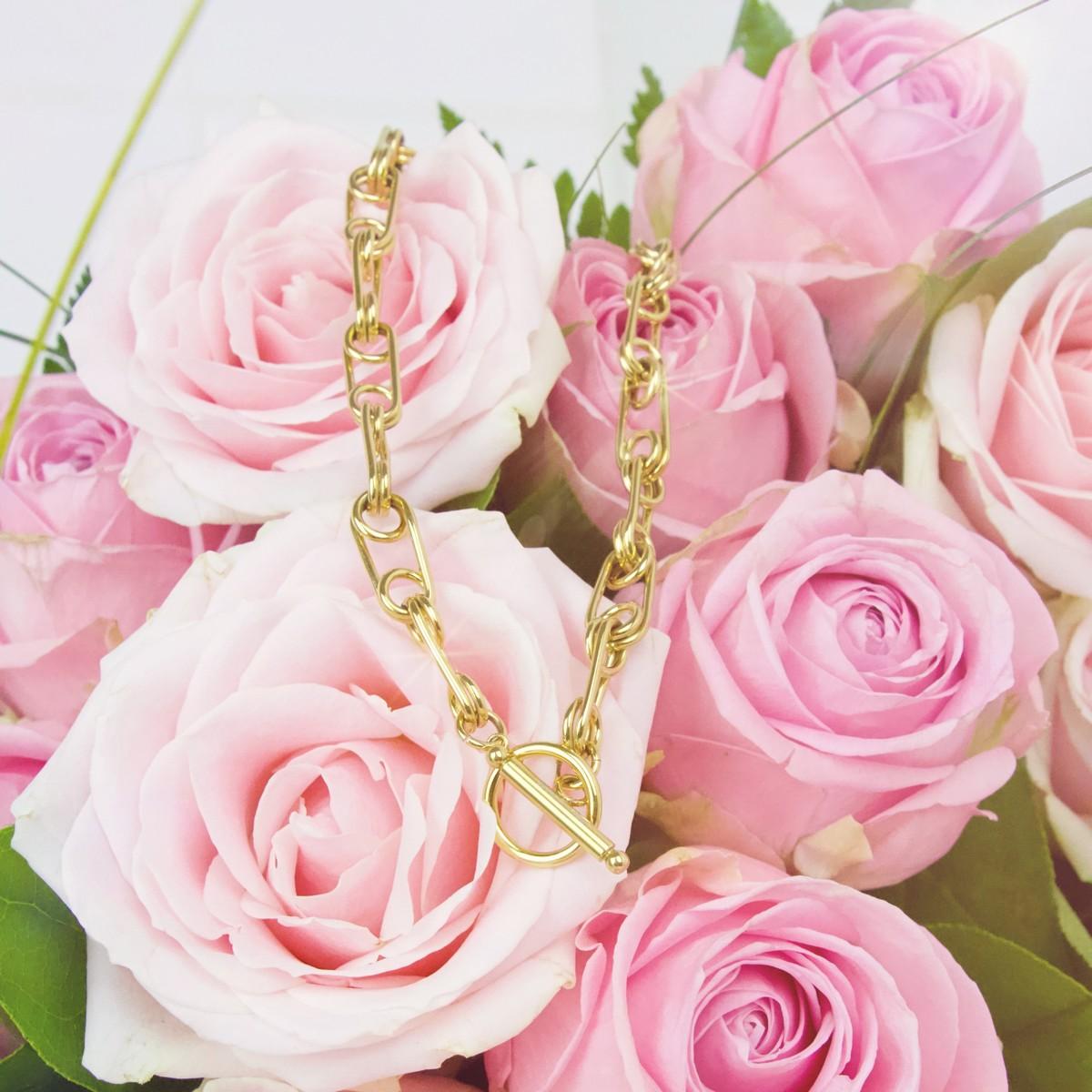 collier doré Hazanellie sur bouquet de roses